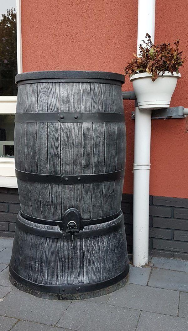 Grijze houten regenton 120 liter aangesloten op regenpijp